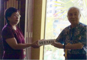 new Rotary member Tin May accepting We Rotary donation.5